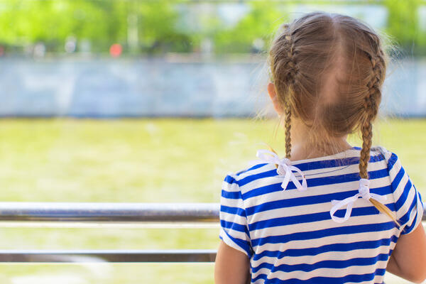 Little girl with braids looking out towards the water on the balcony of a river cruise ship