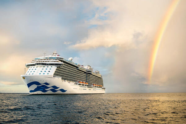 Princess Cruises ship a sea during sunset, with a rainbow in the background