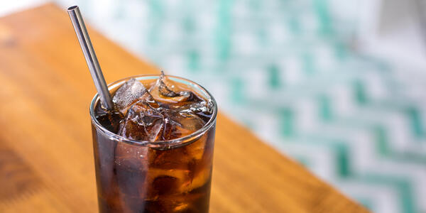 Reusable Metal Straw in Glass Filled With Soda (Photo: VDB Photos/Shutterstock)