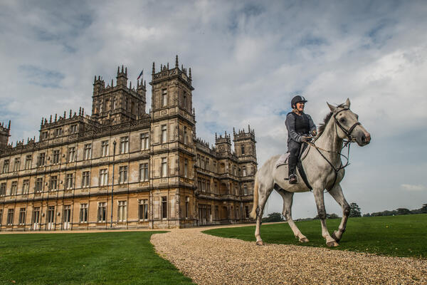 Moody exterior shot of a woman riding a light grey horse in front of Highclere Castle