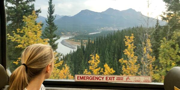 Woman looking out a train window at the landscape between Denali and Whittier