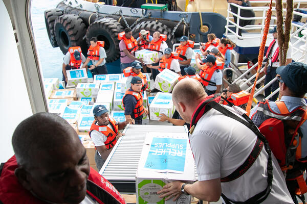 Symphony of the Seas' crew members unloading relief supplies and meals for distribution at Grand Bahama