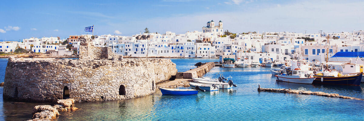 Picturesque Naousa village in Paros, Greece with white buildings, clear waters and bright blue skies