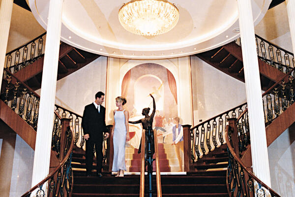 Couple dressed up for formal night on the grand staircase of the Main Dining Room on Navigator of the Seas