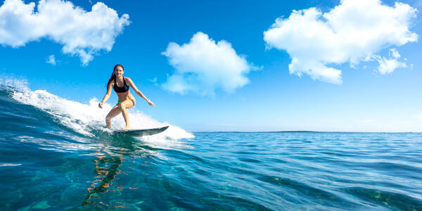 A Young Girl Surfing on a Blue Wave (Photo: ohrim/Shutterstock)