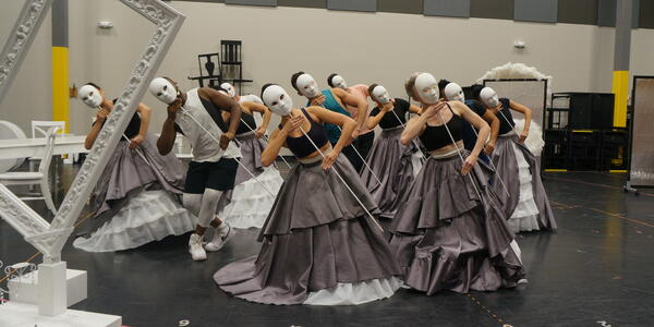 Cast rehearsing Celestial Strings with costumes and masks