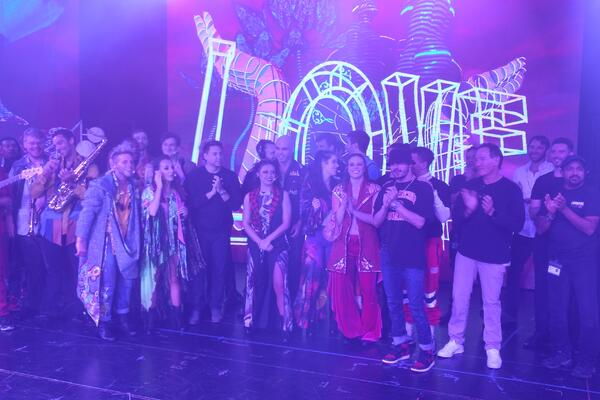 Cast with creative team of Rock Revolution standing together on stage after the performance