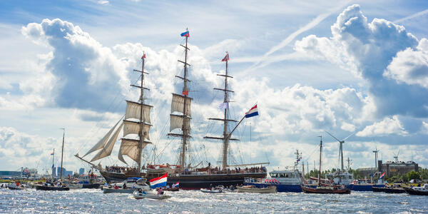 Sailing boats on river during Sail Amsterdam (Sail In), Netherlands, with beautiful sky (Photo: Elisabeth Aardema/Shutterstock)
