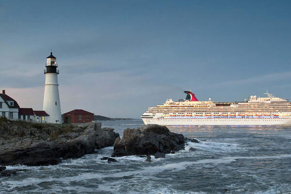 Carnival Cruise Line ship cruising past a rocky jetty and lighthouse in Cape Elizabeth