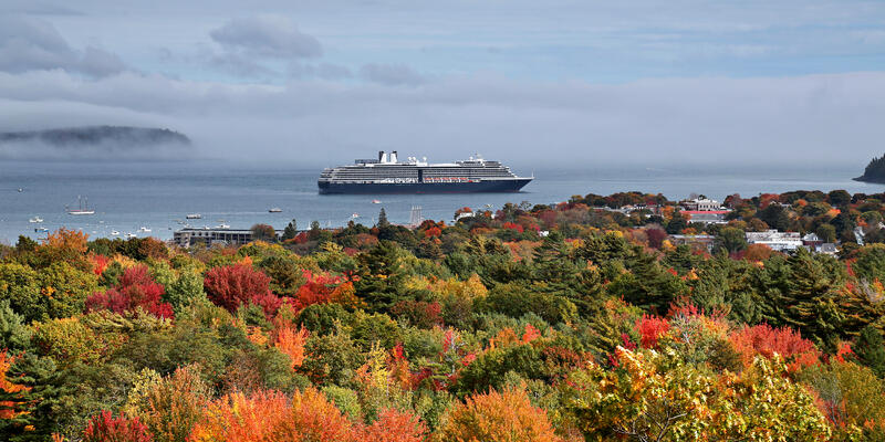 Holland America vessel cruising near fall foliage on a cloudy morning (Photo: Randall Vermillion/Shutterstock)