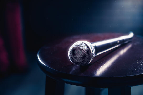 Microphone on a wooden stool on a stand up comedy stage (Photo:Fer Gregory/Shutterstock)