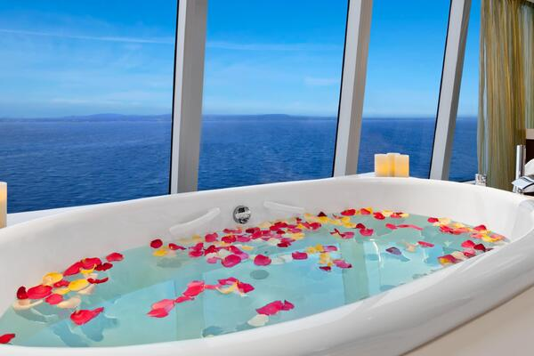 A bath tub filled with water and rose petals overlooking the ocean inside the Aquamar Spa