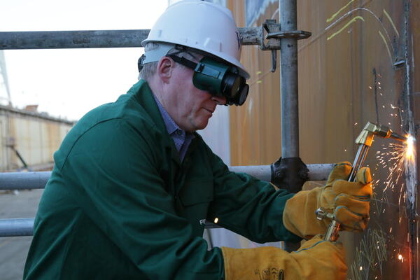 Windstar President John Delaney wearing safety goggles and a helmet, making the final cut to Star Breeze