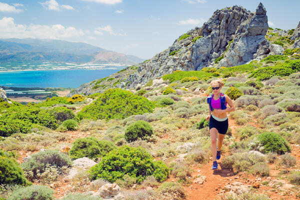 Woman jogging on track in the mountains on a sunny day (Photo: Blazej Lyjak/Shutterstock)