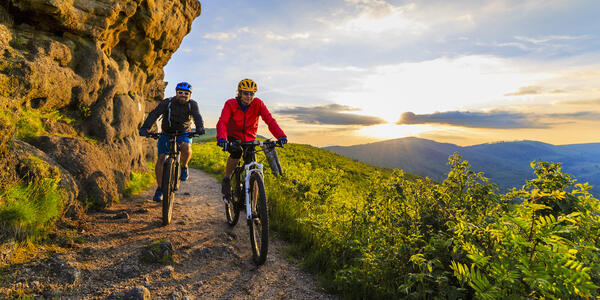 Couple biking on excursion with the sunset in the distance (Photo: gorillaimages/Shutterstock)