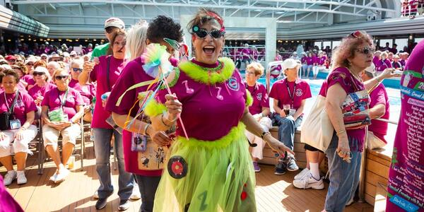 Female passenger dressed in a pink and green costume, smiling, onboard The Malt Shop Memories Cruise
