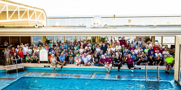Group of passengers posing for a photo on the pool deck onboard The Malt Shop Memories Cruise