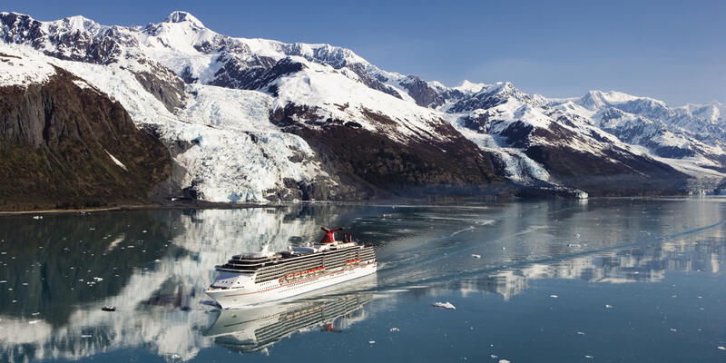 Aerial shot of a Carnival cruise ship sailing past snow-covered mountains and glaciers