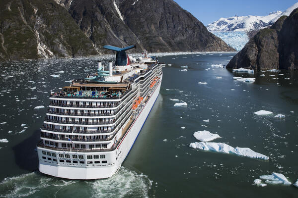 Aft view of Carnival Miracle sailing in the icy waters of Alaska, surrounding by snow-capped mountains