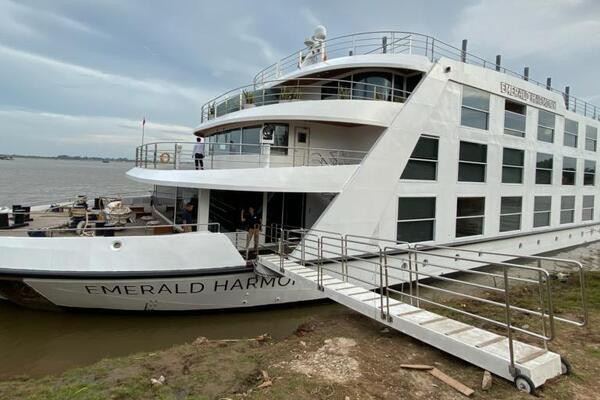 Wide-angle exterior shot of Emerald Harmony docked on a muddy bank along the Mekong