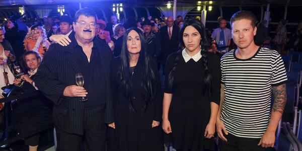 Four people dressed up as the Addams Family, looking into the camera and not smiling