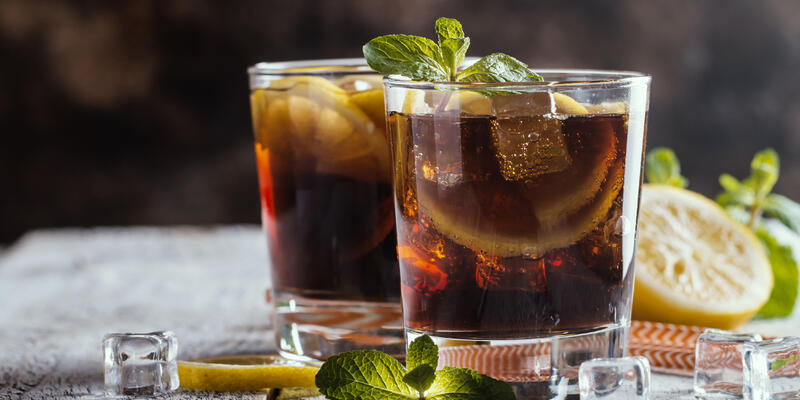Fresh made Cuba Libre with brown rum, cola, mint and lemon on wooden background (Photo: Goskova Tatiana/Shutterstock)
