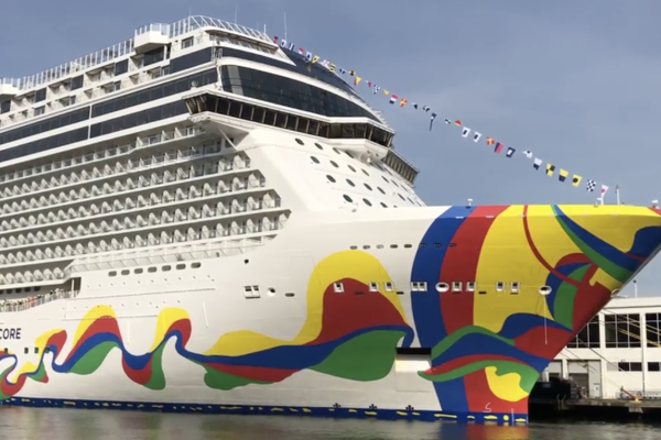 Exterior shot of Norwegian Encore docked at the Manhattan Cruise Terminal on a sunny afternoon