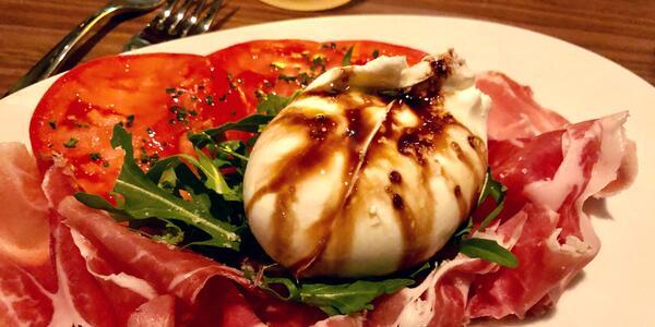 Close-up shot of a burrata, arugula and prosciutto dish on Norwegian Encore