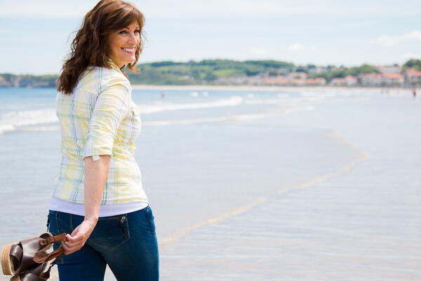 Middle aged woman walking along the shore holding shoes in hand (Photo: asife/Shutterstock)
