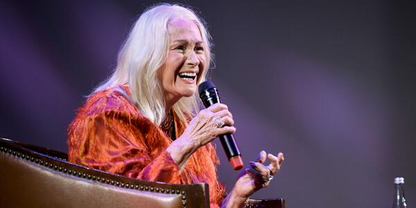 Close-up of a sitting Diane Ladd smiling and speaking into a microphone onstage