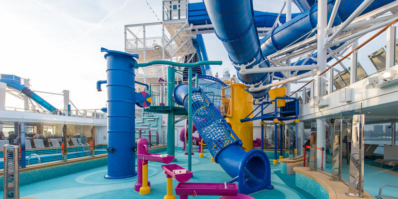 Shot of the colorful pool and slides at the Aqua Park on Norwegian Encore on a cloudy day, without passengers
