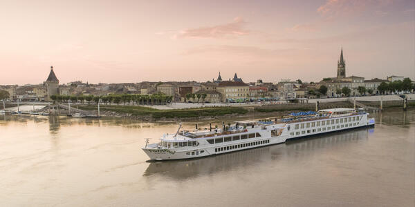 Exterior drone shot of S.S. Bon Voyage cruising along a river at sunset