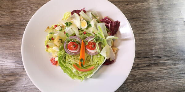 A plated salad in the shape of a face