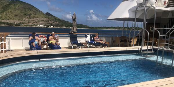 SeaDream II's swimming pool with passengers on sun loungers.