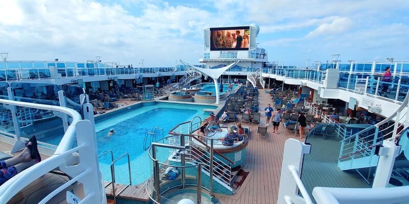 Wide-angle shot of the Sky Princess pool deck on a sunny day, with passengers