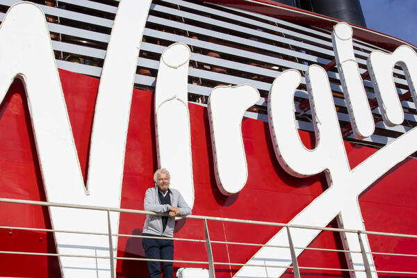 Richard Branson posing with the bright red Virgin Voyages funnel