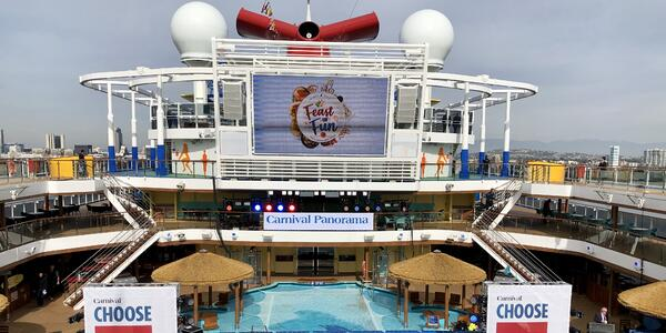 Wide-angle shot of Carnival Panorama's Pool Deck, with christening decor and stage in the frame