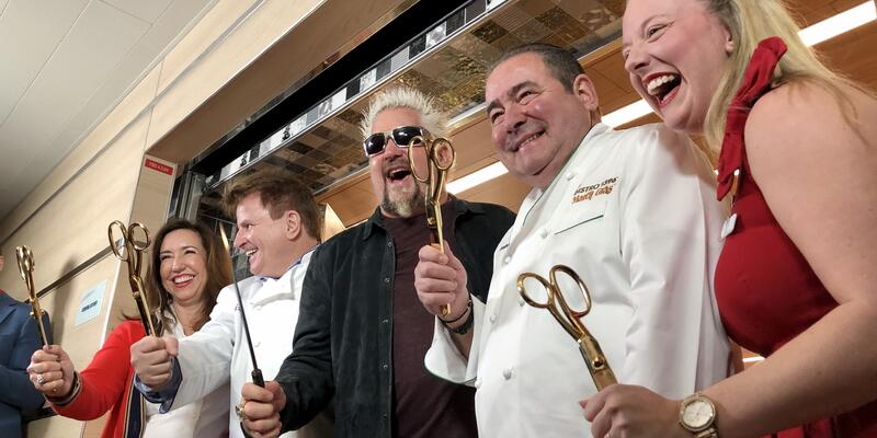 Christine Duffy, Rudi Sodamin, Guy Fieri and two other people smiling and holding gold scissors at the culinary ribbon-cutting ceremony on Carnival Panorama
