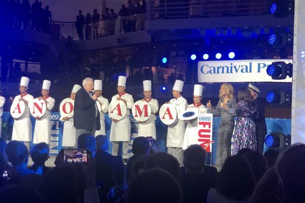 Chefs holding up plates that spell