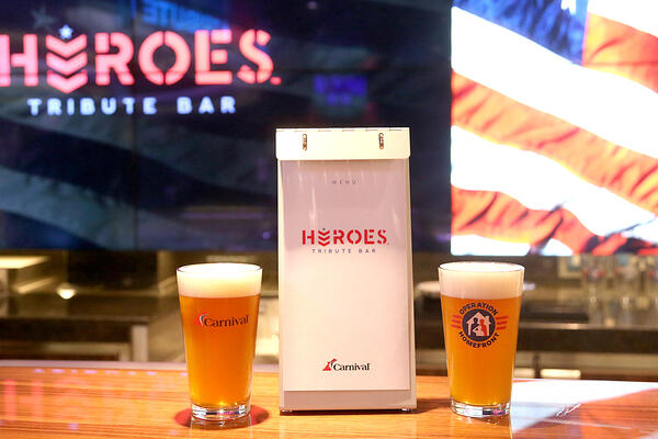 Shot of two pints of beer and a menu on the bar at Heroes Tribute Bar on Carnival Panorama
