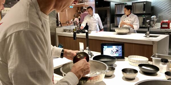 Shot of a passenger mixing a bowl of ingredients at Culinary Kitchen, with chef instructors in the background