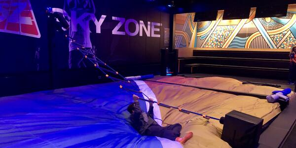 Male passenger holding onto a rope ladder at the SkyZone Trampoline Park