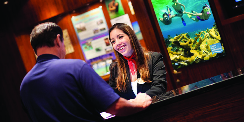 Passenger and concierge worker at the shore excursion desk of a Norwegian cruise  (Photo: Norwegian Cruise Line)