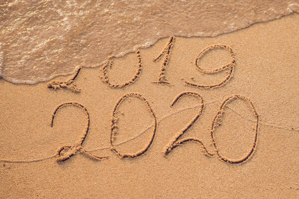 New Year 2020 is coming concept - inscription 2019 and 2020 a beach sand, the wave is almost covering the digits 2019 (Photo: Elizaveta Galitckaia/Shutterstock)