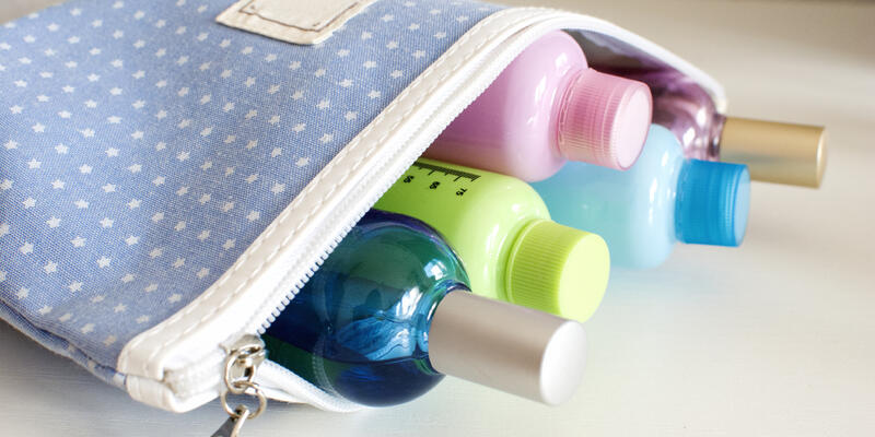Close-up shot of an open toiletry bag, filled with small bottles of soap and shampoo