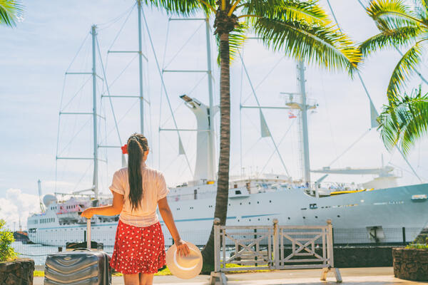 Young woman with a suitcase in the Caribbean, looking at a cruise ship in port