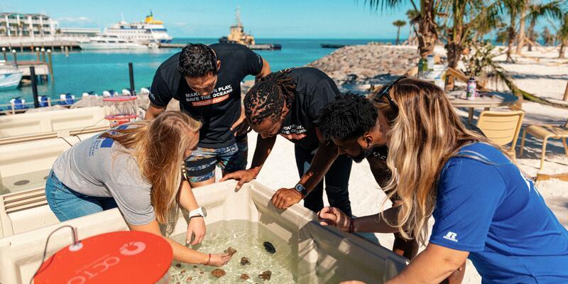 Ambassadors gathered around a coral tank at Ocean Cay MSC Marine Reserve
