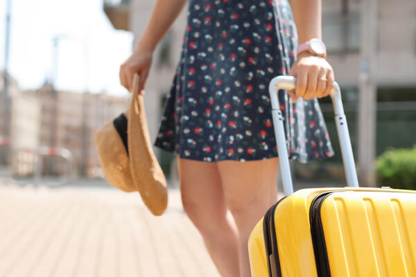Young woman with yellow carry-on suitcase outdoors