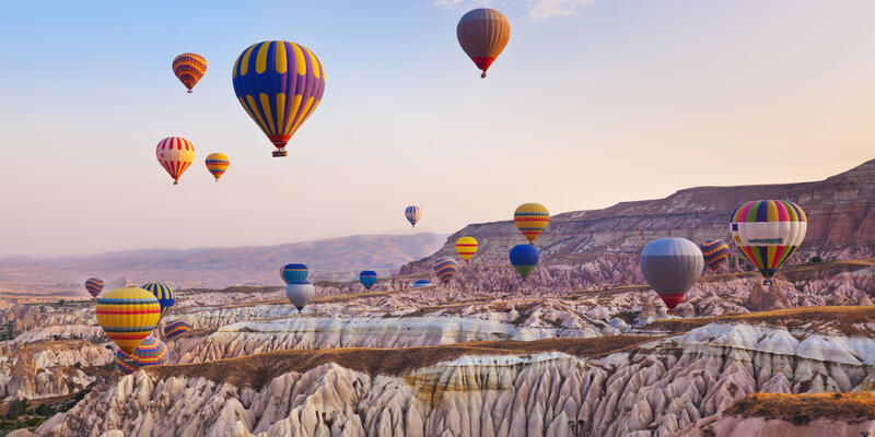 Landscape of Cappadocia, Turkey with lots of hot air balloons in the air