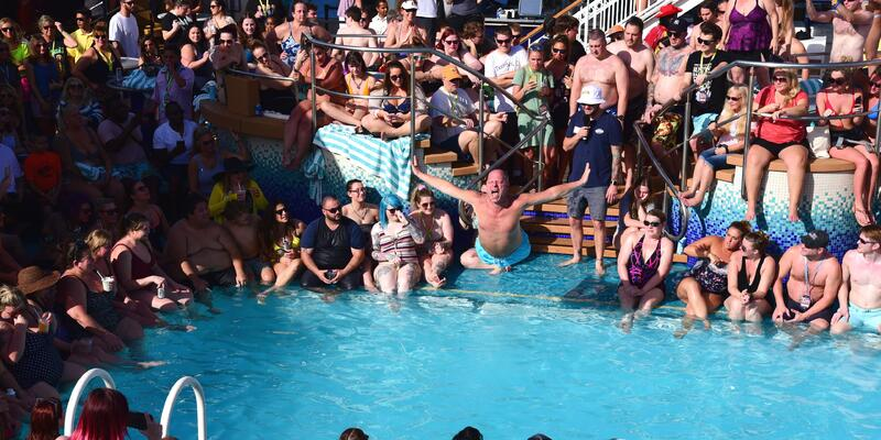 Man in mid-air during Belly flop competition on Impractical Jokers Cruise 4